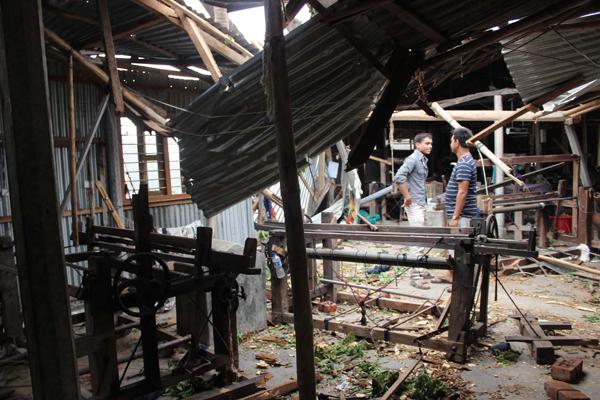 壊れた工房を前に、被害状況を確認するスタッフ